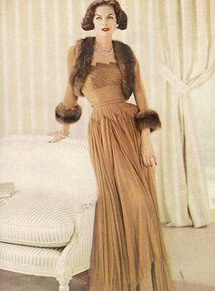 Anne St. Marie in a fur-trimmed bolero jacket worn over matching caramel chiffon gown, 1959