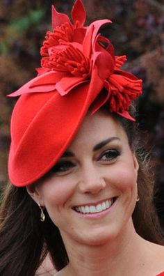 June 3, 2012 - The Diamond Jubilee Flotilla warranted a special hat. Kate chose a red wool hat trimmed in large monochrome wool lilies to compliment her red Alexander McQueen dress.