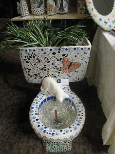 """Wow, this artist did a beautiful job! Recycled toilet """"fountain"""" and planter. I'd like to create a toilet fountain as well...not just use it as a planter. Being a cat lover, I love that little touch...and I have just the 'peeking cat' statue to use :)"""