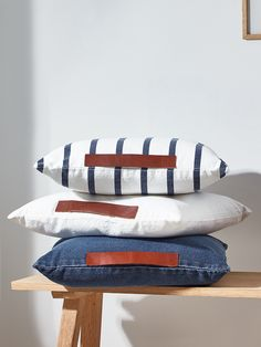 Our set of three nautical inspired cushions are made from 100% cotton in three different designs; simple white, navy and white striped, and denim blue. Each cushion includes a stylish red brown leather detail along the top, and arrives sumptuously filled.