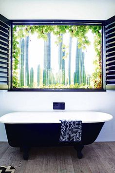 Black cast iron tub in bathroom with view of cactus garden Minimalist Bedroom, Minimalist Home, Stone Mansion, Cast Iron Bathtub, Luxury Bathtub, Cabin Bathrooms, Dream Bathrooms, Bathroom Remodel Cost, Bathroom Renovations
