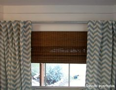 White plank wall, woven wood blinds, chevron curtains and a galvanized rod.