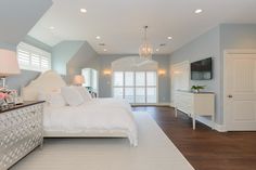 Bedroom :white and blue master bedroom, cream wooden bed,white ruffle bedding, silver infinity chest, silver scroll chest, silver dressers, silver nightstands, cream rug,TV across from bed,crystal chandelier.