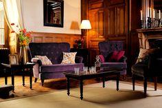 Meubles Demeure http://www.comptoir-de-famille.com/fr/catalogsearch/result/?q=demeure et Domaine http://www.comptoir-de-famille.com/fr/catalogsearch/result/?q=domaine composés d'un ensemble d'assises capitonnées couleur aubergine et de meuble acajou.
