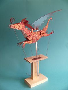 This Dragon automata has been hand cut from aluminium and painted in red. It has then been stamped in gold. When the handle is turned it moves with a realistic flying motion. Each one is signed and numbered by the artist. It is 15 high