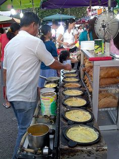 "Vendor selling traditional sweet 'kuih apam' in a Malaysian night market. In Indonesia this sweet cakes are called ""martabak manis"" or ""terang bulan"" (full moon)!"