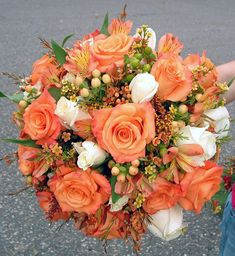 orange and ivory rose, hypericom, and waxflower bridal bouquet