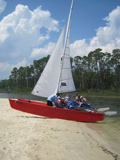 Sailing. Red boat with white sails. The perfect way to spend the day together on the water.