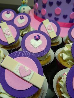 Cute purple Doc McStuffins cupcakes and cake with hearts and bandages