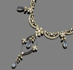 An aquamarine and seed pearl necklace, circa 1900.  Set to the front with a ribbon of floral and foliate design, suspending a navette-shaped openwork pendant and pear-shaped aquamarine drops, set throughout with seed pearls, to a gate-link backchain, length 39.0cm, fitted case by The Goldsmiths & Silversmiths Company Ltd, 112 Regent St London W