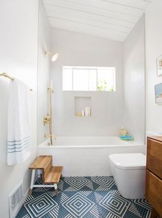 Emily Henderson's guest bathroom featured our Chaine Homme tiles in White Gloss on the shower walls and tub surround.