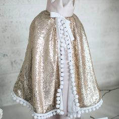 A beautiful, luxury addition to your little one's dressing up box.A wonderfully lux play cape, made from golden sequins and soft white cotton. Our new capes feature a safety release, adjustable cotton tie and 100% cotton inner lining. They look beautiful over dresses or teamed with a Peter Pan collar, and come gift wrapped in Fable Heart box and starry tissue paper. Suitable for ages 3-7 years.Sequin mesh fabric, 100% cotton.100 x 40