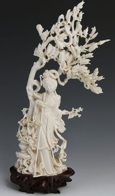 """CHINESE CARVED IVORY BEAUTY UNDER TREE WITH BASE Chinese carved ivory female beauty figurine standing under blossoming tree. Elaborately dressed wearing flowing robes and figural hair ornament with large staff used to pull blossom from tree in hand. Beside her is a woven basket with flowers she has collected. Attached to wooden base. Weight: 481g with base Size: 12.75"""" with base"""