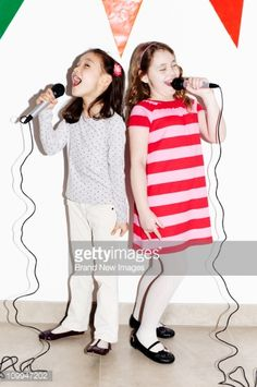 Stock Photo : Girls singing into microphones at party