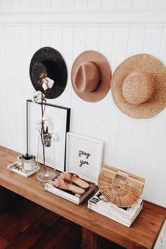 how to style a bench // art work, magazines, and hang hats above the bench
