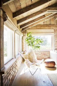Brick walls, white chair, fuzzy cushion, bean bag chair, rug, large windows