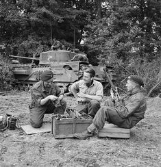 Lt Fathergill, CO of 'B' Squadron, 107th Regiment Royal Armoured Corps, 34th Tank Brigade, with two of his crew cleaning a Besa machine-gun in front of their Churchill tank. Normandy, 17 July 1944.
