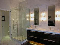 As seen on HGTV, this modern bathroom features a glass-enclosed shower and an entire wall of marble.
