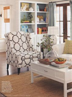 I love everything about this living room!  White walls, woven rug, pattern, wood doors, linen drapes, pops of color (BHG Oct 2012)