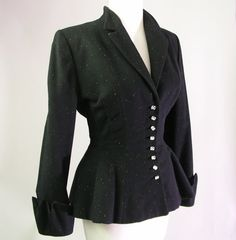 1940s black wool Lilli Ann jacket. The fabric was imported from France. It has speckles of color thread throughout, has crystal rhinestone buttons, zig zag shaped cuffs, peplum waist and silk or rayon lining.