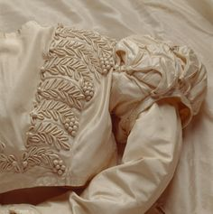 Detail of the white silk wedding dress worn by Mary Elizabeth Williams when she married George Hammond Lucy at Charlecote Park, Warwickshire