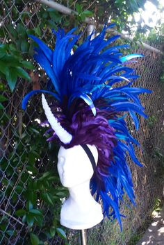 The Unicorn headdress is made with blue, turquoise and purple feathers. The horn is hand cast from solid resin, not one of the cheap plastic shell horns you find at party/halloween stores. This guys is solid!  The mohawk is very light weighing in at 11 ounces!! They don't put any weight on your neck and it is easy to forget you are even wearing it. Watch out for low door frames and ceiling fans.  The mohawk is extremely secure once it is on. People have worn them to concerts and they…
