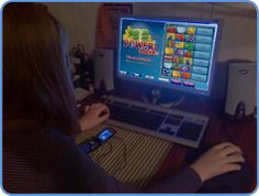 Woman playing Power Cash scratch card game using personal computer, at the convenience of her house. http://www.best-games-directory.com/scratch-card.html