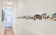 Love this idea for a narrow hallway.  Just line up a ton of photos (here, they are printed as Polaroids) on an even sightline.  Fantastic!
