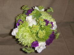 Bridesmaid bouquet with roses, trachelium,spider mums, mini carns and filler. wrapped with ribbon and silver wire.