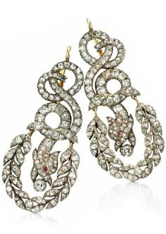 A Pair of Late 19th Century Diamond Ear Pendants. Of chimera design set throughout with old-cut cushion shaped diamonds, the scrolling tapered body and tail surmount suspending the central head motif and surrounding laurel garland drop, open-set in silver and gold, circa 1880. #Victorian #BelleEpoque #earings