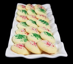A photo of various short bread christmas cookies decorated with red and white candy cane sprinkles and green sprinkles.