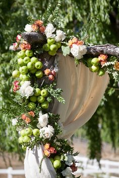 A lush chuppah with apples and roses for an outdoor spring wedding | @mayamyersphoto | Brides.com