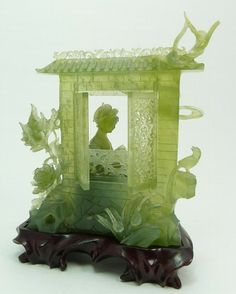 "A nicely carved Chinese translucent green serpentine jade sculpture depicting a meiren playing a zheng. Behind her is wall with moving reticulated windows. Surrounded by foliage and flying birds. Includes fitted wooden base. Circa 19th/20th century. 7 1/4"" height x 6"" width (18.4cm x 15.2cm). Jade weight of 528 grams."