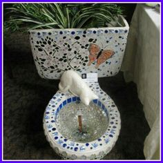 Mosaics toilet. Tank has been used to grow plants. A kitty statue pretends to drink fresh water.
