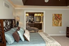 Spacious master bedroom design by 3 Pillar Homes. This master bedroom features a deep angled tray ceiling, an open floor plan and loads of windows to bring in the natural light. Our craftsmanship is shown here with crown molding, trim around the door, and oversized baseboards.