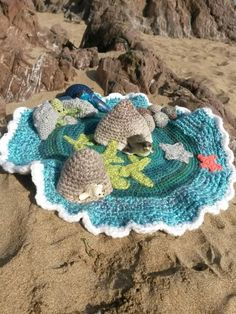 Crochet playmat with a beach and ocean theme, perfect for little characters to hide in