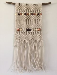 A one of a kind handmade macrame wall hanging. 12 wide x 26 long (branch not included in width, fray is included in length) Made with cotton macrame cord and wood beads.