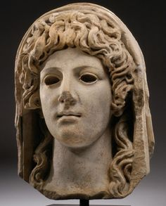 ROMAN MARBLE OVER LIFE-SIZE VEILED HEAD OF A GODDESS, possibly Persephone, daughter of Zeus and Demeter. The eyes of this superb head are recessed for inlay; retaining some original pigment, especially in the hair. 1st Century BC/AD.