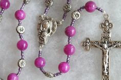 ☧ Catholic Prayer Beads / Religious Jewelry / Handcrafted rosary ☧  This is a beautiful handmade Floral and Violet rosary. This piece was handmade using Holy Trinity crucifix and a beautiful Madonna centerpiece.  *** ✞ ***  This rosary has Violet Candy Jade beads (15 beads, 8mm) and 13 silver floral beads Measures: 1 Decade Total length is 13 Inches Crucifix is 1.5 inches tall  *** ✞ ***  Your item will be ready for shipping within 1-3 business days.  All Rosaries come hand packed i...