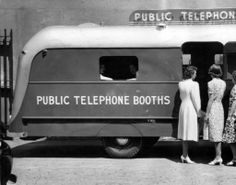 Women stand outside of Bell Telephone Company's new trailer equipped with public telephone booths. Philadelphia, circa 1940