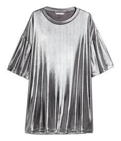 Silberfarben. Gerade geschnittenes Kurzarmshirt aus metallisch schimmerndem Jersey. Das Shirt hat überschnittene Schultern.
