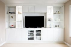 Clean white wall-to-wall shelving system to display family photos, television, books, and games. Media Room Design, Wall Design, Wall Shelving Systems, Cleaning White Walls, Small Media Rooms, Display Family Photos, California Closets, Media Wall, Custom Cabinetry
