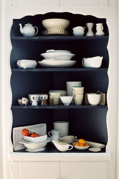 White painted corner cabinet with black painted inside... and white things on shelves.  I like this.