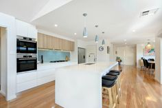Open plan kitchen to dining. Light blue glass splashback, polytec oak ravine and white cabinets. Blackbutt wood floors.