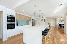 Open plan kitchen to dining. Light blue glass splashback, polytec oak ravine and white cabinets. Blackbutt wood floors.