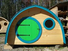 Hobbit Hole Playhouse with round front door and windows, cedar roof, all natural wood construction, turquoise and lime green trim
