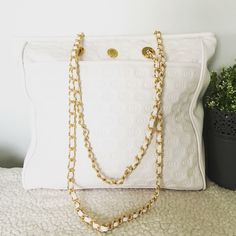 White quilted tote bag Elizabeth Arden Tote Bag ·         Faux leather ·         White ·         Gold chain strap ·         Zip closure ·         Large pocket on front ·         Interior zipper pocket ·         Minor scratching as pictured ·         Small transfer mark at top (pictured) ·         Measures 12x3x11.5 ·         Strap 12.5 Elizabeth Arden Bags Totes