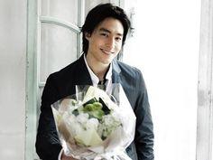 A man bearing flowers!