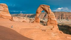 Couple sitting on the rocks along one of the best hikes in Arches Delicate Arch...