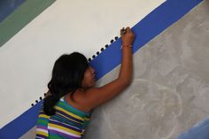 This girl from Peru is painting on the wall of her orphanage. This mural painting inspired us for the 2015 collection. A percentage of the sales are given back to the children so they can get have an education.